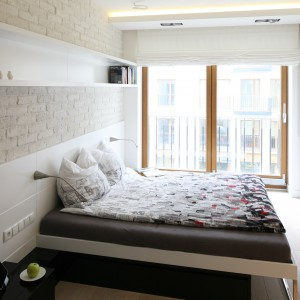 Cegłę na ścianie i białe wyposażenie tej sypialni ociepla nie tylko drewniana podłoga w jasnym kolorze, ale również nieco ciemniejsze framugi okien. Oczywiście również drewniane. Dzięki tym elementom nowoczesna sypialnia nie jest sterylna ani zimna. Projekt: Monika i Adam Bronikowscy. Fot. Bartosz Jarosz.