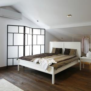 Ta przestronna sypialnia na poddaszu urządzona jest w nowoczesnym stylu. Dominują tu lekkie, proste formy i biała kolorystyka, którą ocieplają ciemne, dębowe deski na podłodze. Projekt: Konrad Grodziński. Fot. Bartosz Jarosz.