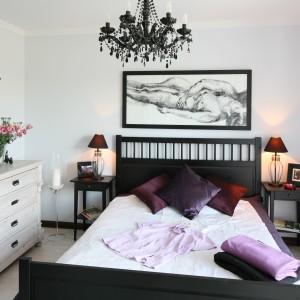 To elegancka, przytulna sypialnia z lekkim akcentem glamour – co szczególnie widać w zastosowanym oświetleniu. Jasne drewno na podłodze doskonale pasuje do komody, stanowi natomiast ładny kontrast z ciemną, drewnianą ramą łóżka i szafkami nocnym. Projekt: Magdalena Kwiatkowska. Fot. Bartosz Jarosz.