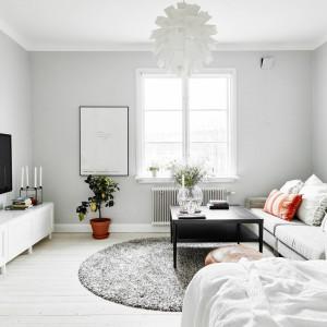 Ze względu na mały metraż mieszkania salon połączono z sypialnią. Przestrzeń dzienną wyznacza okrągły dywan. Fot. Stadshem/Jonas Bergman.