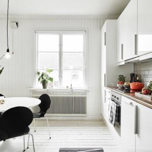 Przestrzeń kuchni, połączono z jadalnią. To tutaj wkomponowano elementy w mocnej czerni, nadające charakter białemu wnętrzu. Krzesła harmonizują kolorem z okablowaniem dekoracyjnej żarówki. Fot. Stadshem/Jonas Bergman.