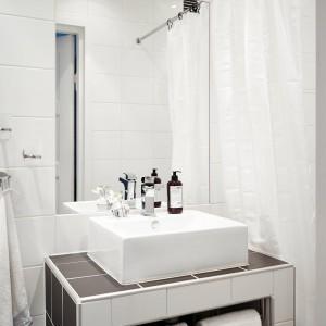 W łazience dominują geometryczne formy. Prostokątne, proste lustro idealnie komponuje się z kubistyczną umywalką oraz zabudową podumywalkową. Fot. Stadshem/Jonas Bergman.