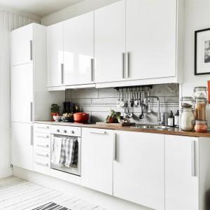 Meble kuchenne utrzymano we współczesnej stylistyce. Gładkie powierzchnie wykończone na wysoki połysk, zwieńczono prostokątnymi, metalowymi uchwytami. Nad blatem roboczym zamontowano funkcjonalne relingi, a ścianę wykończono jasnoszarymi płytkami. Fot. Stadshem/Jonas Bergman.