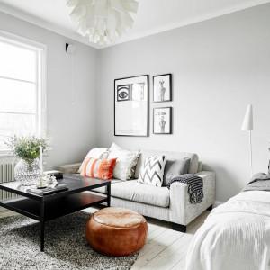 Część salonową łączonej przestrzeni pokoju dziennego i sypialni wpasowano w róg pomieszczenia. Zaznaczają ją obrazki na ścianach, szara sofa, hojnie udekorowana tekstyliami, czarny stolik kawowy i brązowy puf. Fot. Stadshem/Jonas Bergman.