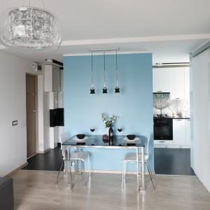 Kuchnię od salonu częściowo oddziela ścianka, poprowadzona przez środek granicy dwóch pomieszczeń. Pomalowana na niebiesko stała się elementem przyciągającym wzrok, zwracającym uwagę na niewielki stół. Projekt: Marta i Tomasz Kilan. Fot. Bartosz Jarosz.
