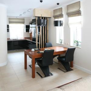 Czarne krzesła komponują się kolorem z meblami kuchennymi. Kuchnię od jadalni dodatkowo oddziela oryginalne przepierzenie, skomponowane z pni bambusa. Projekt: Karolina Łuczyńska. Fot. Bartosz Jarosz.