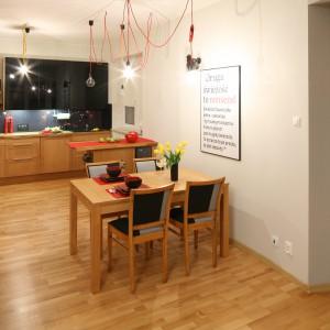 Drewniana podłoga, meble w strefie kuchni i stół jadalniany tworzą spójną całość pod względem koloru i użytych materiałów. Ciemne obicia krzeseł komponują się z górnymi szafkami w kuchni oraz lacobelem nad blatem. Projekt: Izabela Szewc. Fot. Bartosz Jarosz.