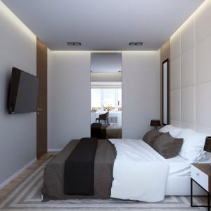 Za wysokim lustrem schowano garderobę. Duża tafla nadaje wnętrzu sypialni głębię i powiększa optycznie przestrzeń. Projekt: Studio projektowe Geometrium.