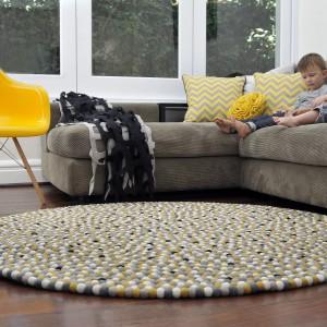 Okrągły dywan, projektu Happy as Larry Design, stworzony z małych pomponów może być jak słońce w aranżacji salonu. Szczególnie, że w jego strukturze znalazły się kuleczki w żółtym kolorze. Fot. Happy as Larry Design.