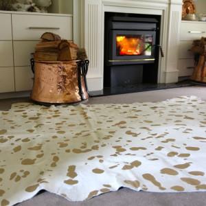 Skórzany dywan z połyskującymi detalami to propozycja do wnętrz w stylu glamour. Złote cętki niesiono w miejsca, gdzie wcześniej usunięto sierść (metodą trawienia). Fot. Two Girls And A Container.
