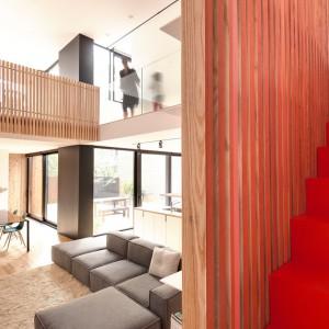 Przestronny jasny salon z wysokim sufitem został otwarty na drugą kondygnację. Duże, panoramiczne przeszklenia, ażurowe, drewniane panele, przez które prześwituje światło oraz przeszklona balustrada na antresoli nadają wnętrzu lekki charakter. Projekt: la SHED Architecture. Fot. Maxime Brouilette.