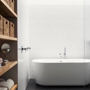 Łazienka na piętrze zyskała przeszklony sufit, przez który do wnętrza wpada duża ilość naturalnego światła, odbijającego się następnie od białych ścian, rozświetlając całe wnętrze. Projekt: la SHED Architecture. Fot. Maxime Brouilette.