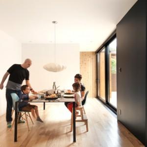Sąsiadująca z kuchnią jadalnia ma bezpośredni dostęp do dużej ilości dziennego światła, wpadającego do wnętrza przez duże przeszklenia. W oszczędnie urządzonym wnętrzu uwagę zwraca mocna czerń na ścianie, efektownie kontrastująca z jasną, drewnianą podłogą i białymi ścianami. Projekt: la SHED Architecture. Fot. Maxime Brouilette.