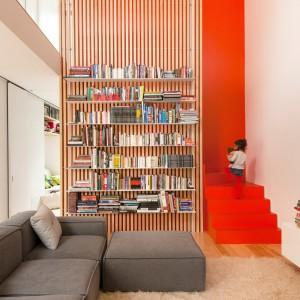 Klatkę schodową, otwartą na salon, schowano za ażurowym, drewnianym parawanem, na którym urządzono biblioteczkę. Jej obecność zaznacza intensywny kolor. Projekt: la SHED Architecture. Fot. Maxime Brouilette.