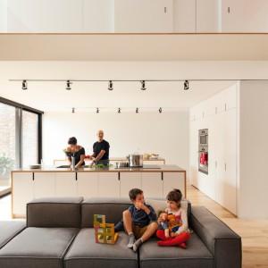 W przestronnej, otwartej na salon kuchni znajduje się bardzo duża wyspa, sprzyjająca wspólnemu przyrządzaniu posiłków przez domowników. Pomieszczenie od salonu można w każdej chwili oddzielić za pomocą przesuwnych ścianek. Projekt: la SHED Architecture. Fot. Maxime Brouilette.