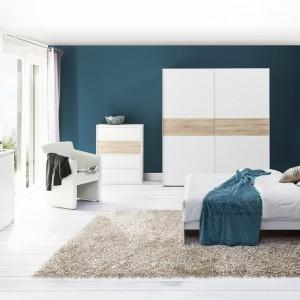 Wenecja to kolekcja złożona z minimalistycznych brył, która  wyróżnia się uniwersalnym połączeniem bieli z dębem sonoma. Brak uchwytów powoduje, że meble nabierają oryginalnego, minimalistycznego wyglądu. Stonowaną aranżację sypialni pięknie ożywia kolor niebieski. Fot. Szynaka Meble.