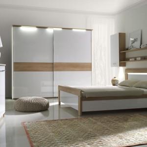 Łóżko Manhattan to połączenie białej, lakierowanej płyty oraz elementów imitujących drewno dębowe. W wezgłowiu umieszczono oświetleniem LED, które wprowadza do sypialni delikatne oświetlenie. Do łóżka w komplecie jest duża szafa, szafki nocne i wiszące oraz komoda. Fot. Stolwit.