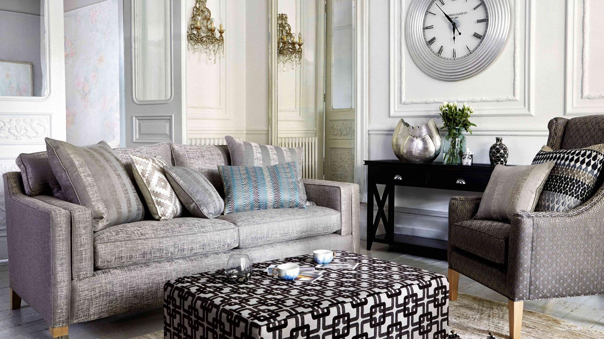Styl klasyczny nie jedno ma imię. Srebrzysta tapicerka mebli oraz wzorzysty stolik kawowy sprawiają, że aranżacja zyskuje nieco glamourowy charakter. Efekt dopełnia biżuteryjne oświetlenie. Sofa Duresta Broadway (widoczna na zdjęciu) dostępna jest w sklepie Furniture Village. Fot. Furniture Village .