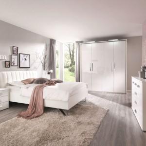 Chociaż sypialnię urządzono wyłącznie białymi meblami, wcale nie jest zimna. Wszystko za sprawą ocieplających detali, drewnianej podłogi, beżowych ścian i dodatków oraz eleganckiej tapety. Fot. Bensons for Bed.