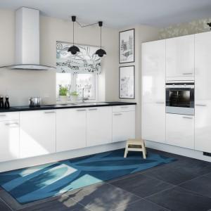 Białe meble utrzymane we współczesnej stylistyce, zwieńczono czarnym blatem, który kolorystycznie komponuje się z oświetleniem nad powierzchnią roboczą. Fot. Nettoline, kuchnia Capri.