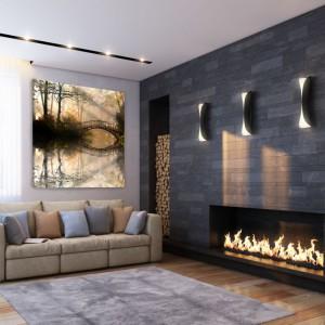 Obraz zaplanowano w ciekawym miejscu - pomiędzy oknem a ścianą z kominkiem. Świetlisty pejzaż w ciepłych barwach korespondujących z ogniem kominka to propozycja ze strony Demur. Fot. Demur.