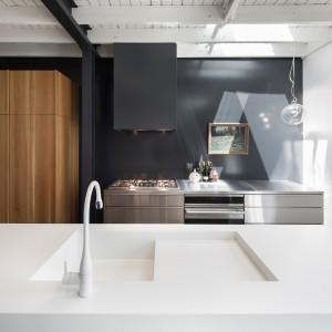 Kuchnia to pochwała nowoczesnej stylistyki. Blat i zlewozmywak wykonane z Corianu, powierzchnia gotowania zamknięta w meble ze stali nierdzewnej oraz okap dopasowany kolorystyką do ściany za nim nadają ton przestrzeni. Projekt: Atelier Moderno. Fot. Stéphane Groleau.