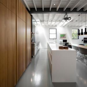 Biało-czarny sufit z wyeksponowanymi belkami konstrukcyjnymi wprowadza do wnętrza element industrialnej stylistyki, nawiązując do oryginalnego przeznaczenia budynku. Wtórują mu loftowe lampy nad stołem w jadalni. Projekt: Atelier Moderno. Fot. Stéphane Groleau.