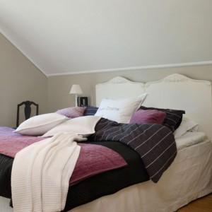 W sypialni urządzonej na poddaszu panuje spokojna kolorystyka. Wnętrze ocieplo tkaninami. Fot. Dulux.