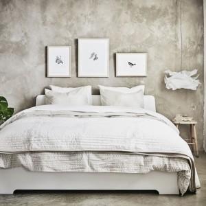 Ściana z fakturą betonu stanowi doskonałe tło dla jasnych mebli, tkanin i dekoracji. Fot. IKEA.