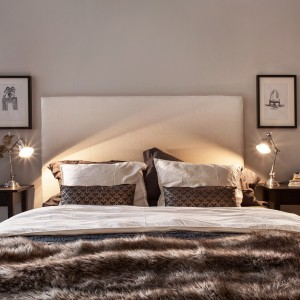 Białe tapicerowane łóżko z wysokim zagłówkiem dobrze prezentuje się na tle szarej ściany. Fot. Fantastic Frank.
