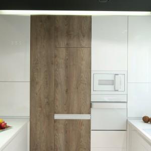 Niewielka powierzchnia 7,5 m2 została zagospodarowana do maksimum. Wysoka zabudowa w kolorach bieli i drewna chowa wszelkie sprzęty AGD, zapewniając porządek wizualny. Projekt: Dominik Respondek. Fot. Bartosz Jarosz.