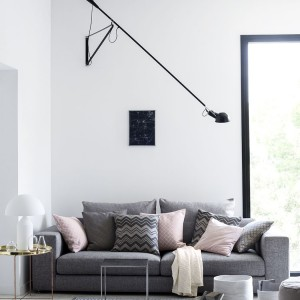 W wysokim loftowym salonie w oczy rzuca się techniczne oryginalne oświetlenie na długim ramieniu oraz kolorowe poduszki. Żakardowe poszewki na poduszki dostępne w H&M - cena 39,90 zł/szt. Fot. H&M.
