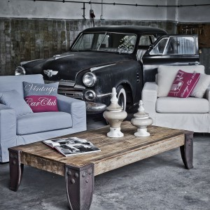 Piękna sesja zdjęciowa marki Almi Decor, prezentująca dodatki w stylu vintage. Elegancki drewniany stół z okuciami oraz ciekawe poduszki z napisami to świetne elementy, które wzbogacą wnętrze. Fot. Almi Decor.