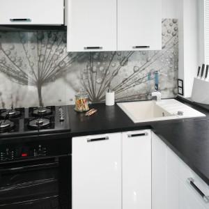Niewielka, zaledwie 3-metrowa kuchnia, została wykończona w bieli, urozmaiconej czarnym blatem i grafiką nad nim. Zlewozmywak wpasowano w przestrzeń w rogu, tak aby uzyskać dłuższą wolną powierzchnię blatu. Projekt: Marta i Tomasz Kilan. Fot. Bartosz Jarosz.