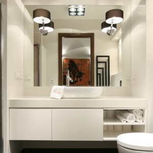 Małej łazience urządzonej w bieli kameralnego charakteru dodają kinkiety z brązowymi abażurami. Ściany wnęki prysznicowej (po lewej) wykończone zostały w kolorze czerwonym, co daje efektowny kontrast i ożywia wnętrze. Projekt: Małgorzata Galewska. Fot. Bartosz Jarosz.