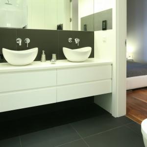Łazienka dla dwojga urządzona tuż przy sypiali. Eleganckie białe meble i wyposażenie wyeksponowano na tle szarych okładzin. Ta kolorystyka zachowana jest również w sypialni.  Projekt: Agnieszka Ludwinowska. Fot. Bartosz Jarosz.