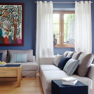 Piękny, kolorowy obraz z ptakami wygląda nieco orientalnie i pięknie komponuje się z ciemnoniebieską ścianą oraz koresponduje z wzorzystymi poduszkami. Fot. Dekoria.