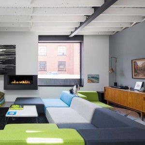 W salonie postawiono na kolorowe akcenty, pięknie prezentujące się na tle stonowanej kompozycji szarości. Turkus i limonkowa zieleń ożywiają wnętrze, a ciepły odcień drewna w połączeniu z ogniem w kominku, nadaje przestrzeni przytulny wyraz. Projekt: Atelier Moderno. Fot. Stéphane Groleau.