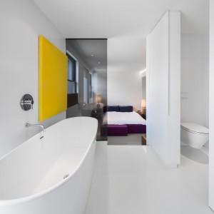 Sypialnię pana domu połączono bezpośrednio z piękną łazienką, pełniącą rolę ekskluzywnego salonu kąpielowego. Dominację bieli przełamano czarnym szkłem, pełniącym rolę elementy działowego oraz żółtym panelem na ścianie. Projekt: Atelier Moderno. Fot. Stéphane Groleau.