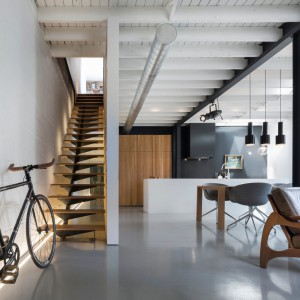 Mieszkanie nawiązuje luźno do industrialnej stylistyki, którą budują belki konstrukcyjne i loftowe oświetlenie. Projekt: Atelier Moderno. Fot. Stéphane Groleau.