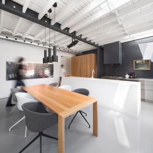 Kuchnię od jadalni oddziela obszerna wyspa kuchenna. Stół jadalniany komponuje się materiałem i kolorem z wysoką zabudową w kuchni. Krzesła z kolei, harmonizują ze ścianami i kolorem wyspy. Projekt: Atelier Moderno. Fot. Stéphane Groleau.