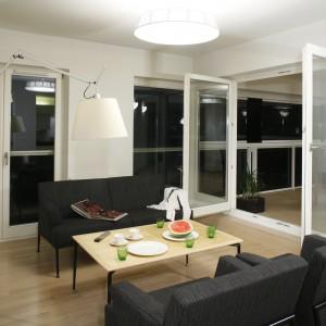 Jasny klosz nowoczesnej lampy na wysokim wysięgniku oświetla niewielki stolik kawowy, ustawiony między dwoma czarnymi sofami. Projekt: Ovotz Design Lab. Fot. Monika Filipiuk-Obałek.