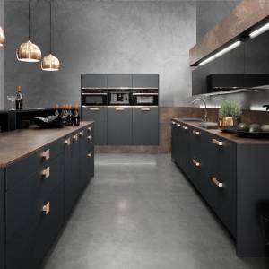 Pasy oświetlenia LED zamontowane u spody górnych szafek. Chłodne światło ledowe efektownie kontrastuje z czernią frontów kuchennych. Fot. Rational, kuchnia Topaz.