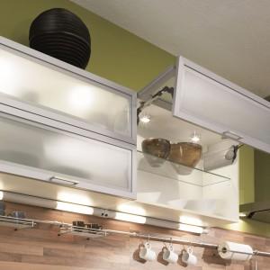 Wewnętrzne oświetlenie zainstalowane w górnych szafkach. Jest praktyczne, ułatwiając lokalizację sprzętów schowanych w szafkach, a także nadaje aranżacji przestrzeni lekki charakter, delikatnie prześwitując przez przeszklone fronty. Fot. Pino, meble z programu PN 230.