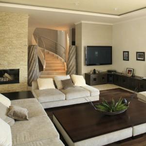 W inspirowanym egzotyczną sztuką dekoracyjną wyspy Bali salon zdominowały jasne barwy w kolorze naturalnego piaskowca. Jego idylliczny wydźwięk przerywa ciemnobrązowy kolor drewna. Projekt: Karolina Łuczyńska. Fot. Bartosz Jarosz.
