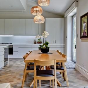 Nad stołem jadalnianym zawieszono efektowne, dekoracyjne lampy z ażurowymi abażurami. Projekt: Daniel Hopwood Studio. Fot. Matt Chung Photo.