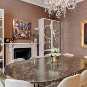 Oprócz stołu jadalnianego w kuchni, dom ma również oddzielną, niezależną jadalnię. Pomieszczenie urządzono w stylu klasyczny, z naciskiem na luksusowe formy i szlachetne materiały. Kamienny blat stołu pięknie harmonizuje z dekoracyjnym żyrandolem nad nim. Projekt: Daniel Hopwood Studio. Fot. Matt Chung Photo.