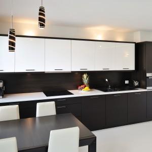 Kuchnię urządzono w oparciu o kontrasty. Białe fronty wykończono na połysk, podczas gdy czarne drzwiczki zyskały elegancką, satynową powierzchnię. Projekt: RS+ Architekci. Fot. Tomasz Zakrzewski.