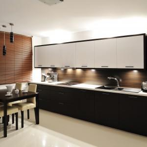 Ścianę nad blatem wykończono płytą z drewnianym dekorem. Kolorystycznie koresponduje ona z bambusową roletą w oknie. Projekt: RS+ Architekci. Fot. Tomasz Zakrzewski.