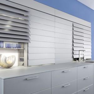 Półki w jednej ze stref przechowywania w tej zabudowie zasłaniane są w innowacyjny sposób - za pomocą frontów w kształcie rolet wykonanych ze specjalnego matowego szkła. Fot. Leicht.